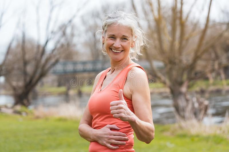 Senior woman giving thumbs-up for sport. Outdoors stock image