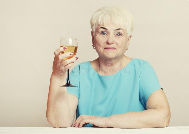 Senior woman with glass of white wine. stock photo