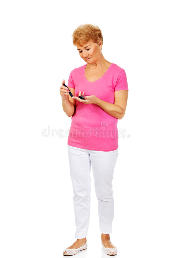 Senior woman with glucometer checking blood sugar level.  royalty free stock images