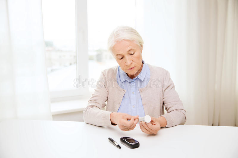 Senior woman with glucometer checking blood sugar. Medicine, age, diabetes, health care and people concept - senior woman with glucometer and test stripes royalty free stock photo