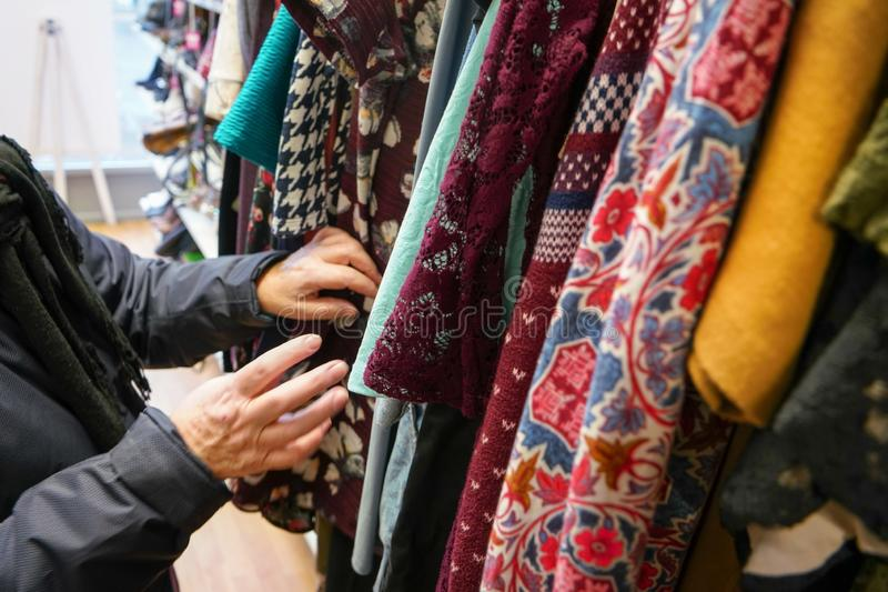 Senior woman going through clothes in second hand thrift charity shop, detail on her moving hands. stock photo