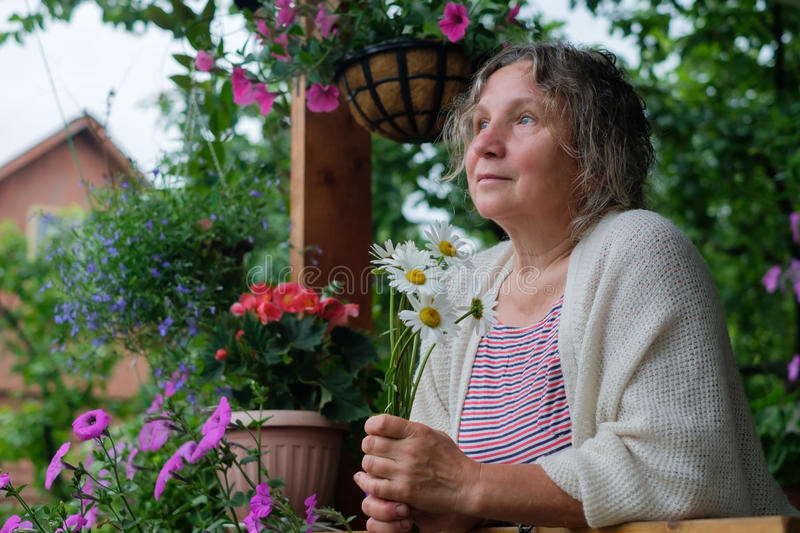 Senior woman in green garden with flowers in hands stock photography