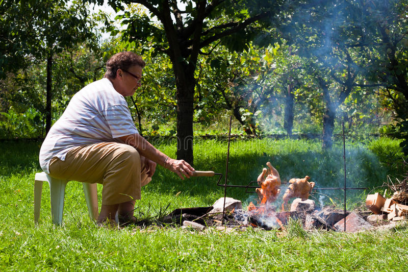 Senior woman grilling chickens. Senior women grilling chickens on bonfire stock photography