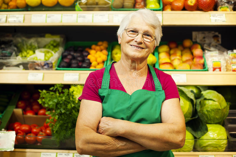Senior woman in groceries store. Senior lifestyle: Portrait of mature store worker stock photo