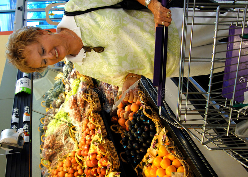 Senior woman in grocery store. A smiling senior woman with a shopping list and cart in the produce section of the grocery store stock image