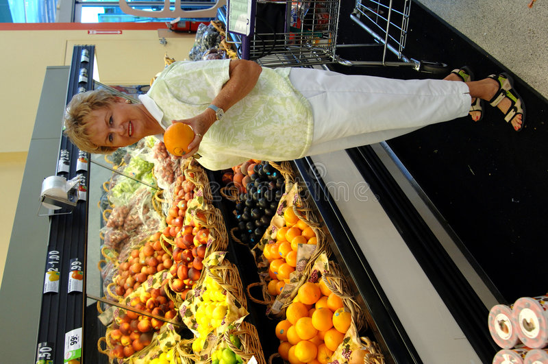 Senior woman in grocery store. A smiling senior woman with an orange in the produce section of the grocery store royalty free stock image