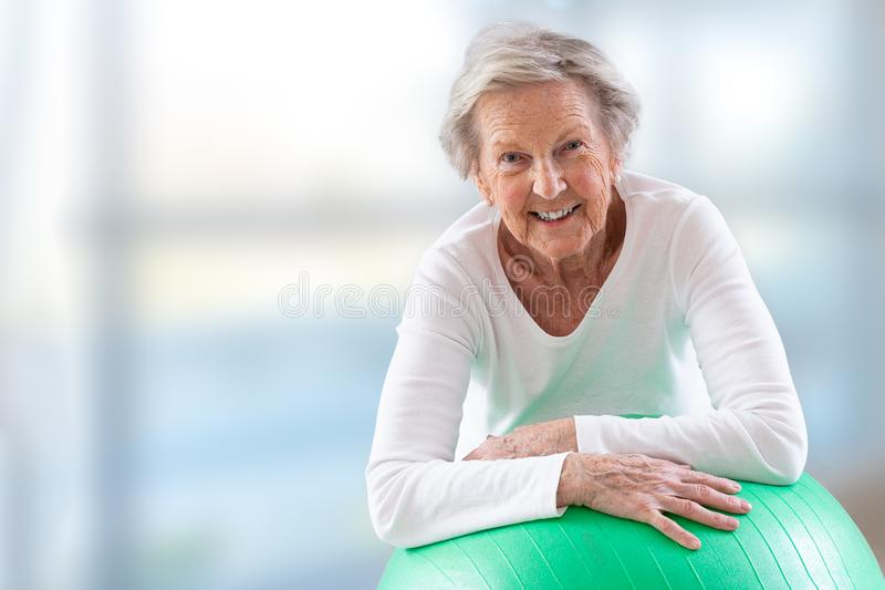 Senior Woman with fitness ball in gym. stock photos