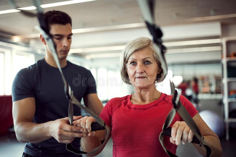 A senior woman in gym with a young trainer doing exercise with TRX. stock images