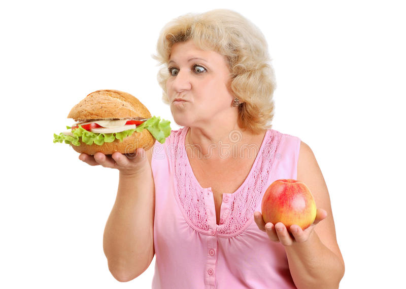 Senior woman with hamburger and apple. Senior woman deciding what to eat a hamburger or an apple isolated on white royalty free stock photos