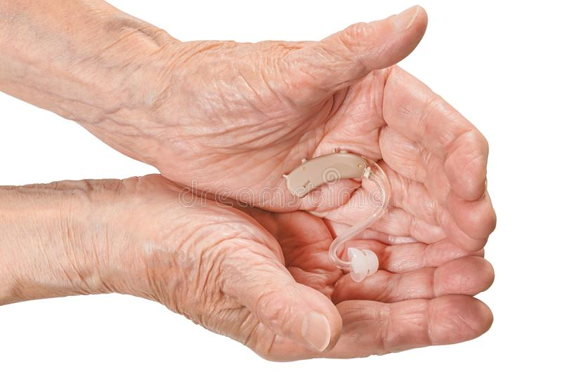 Senior woman hand holding the hearing aid isolated with clipping path stock image
