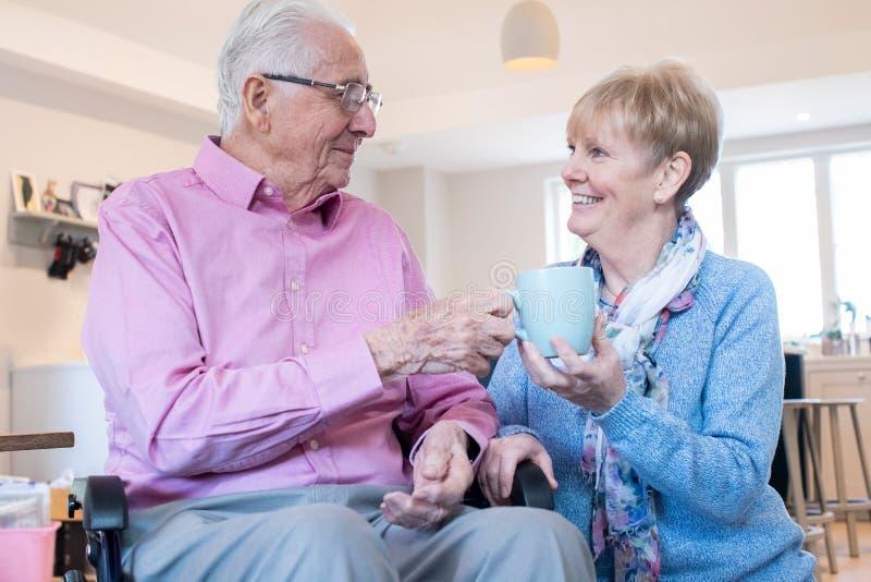 Senior Woman Handing Husband In Wheelchair Hot Drink At Home. Senior Woman Hands Husband In Wheelchair Hot Drink At Home stock photography