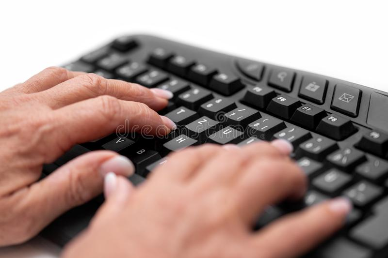 Senior woman hands are correctly touch typing on the keyboard royalty free stock image