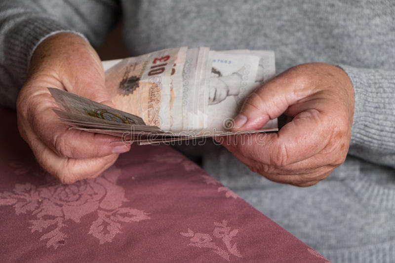 Senior woman hands holding money, UK sterling royalty free stock photo
