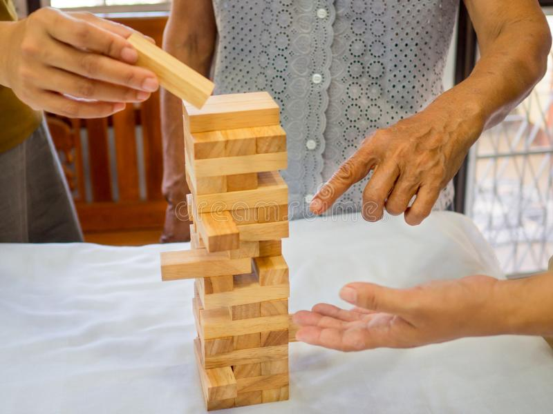A senior woman is happily playing a wooden block game with her family in retirement, Concept Risk management and strategy plan stock image