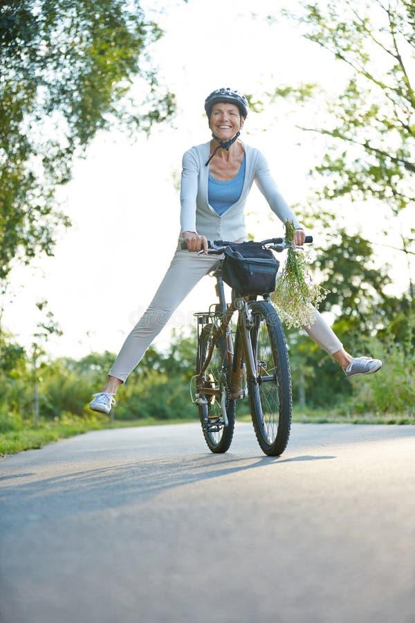 Free Senior Woman Having Fun Riding Her Bike Royalty Free Stock Image - 72954996