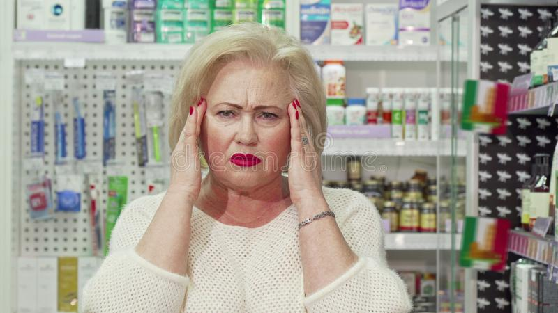 Senior woman having headache, looking for medicine at pharmacy stock photo