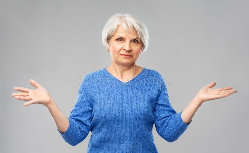 Senior woman having no idea and shrugging stock photo