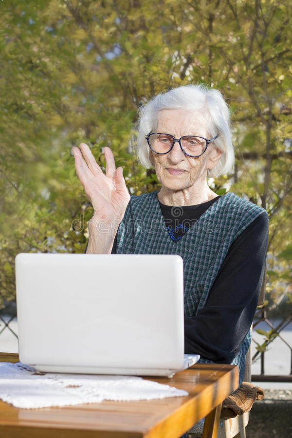 Senior woman having a video call on a notebook computer. In the backyard royalty free stock photos