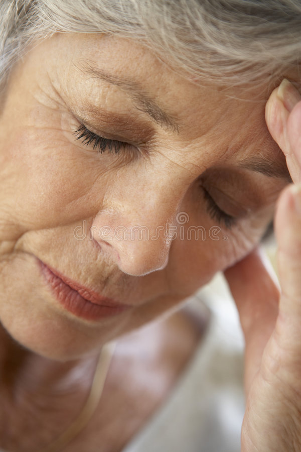 Senior Woman With Head In Hands Looking Weary royalty free stock image