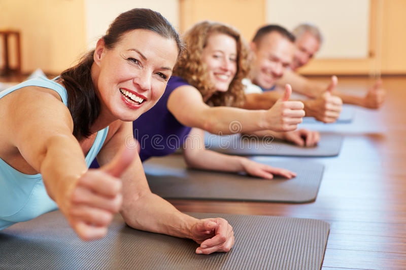 Senior woman in health club holding stock photos