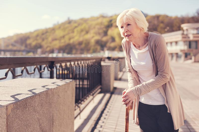 Senior woman heavily leaning on her cane. Contemplating landscapes. Charming elderly lady standing on the bridge and looking on the river while heavily leaning stock photos