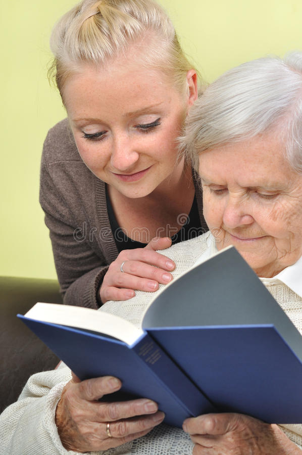 Senior woman with her caregiver. Senior women with her caregiver in home reading book stock images