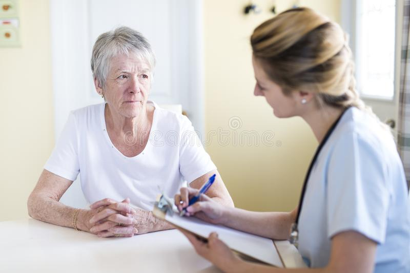 Senior woman with her caregiver at home. A Senior women with her caregiver at home royalty free stock image
