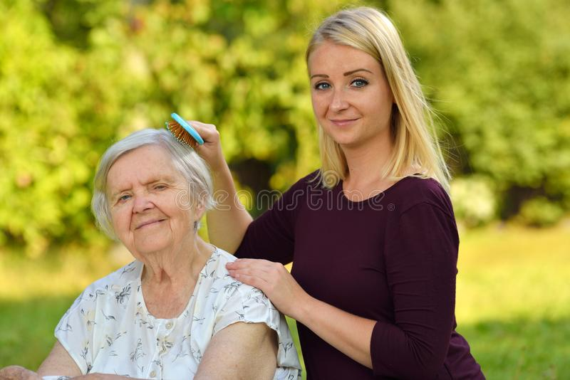 Senior woman with her caregiver. Senior women with her caregiver in park stock images