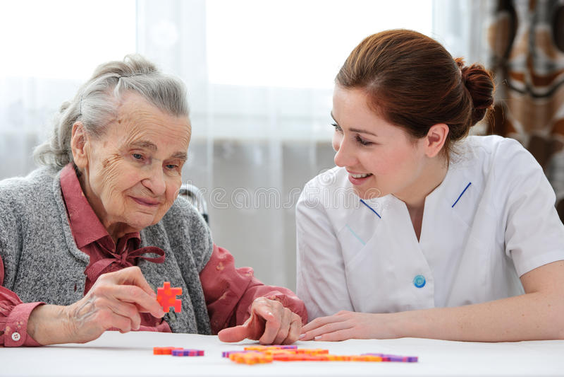 Senior woman with her elder care nurse stock image