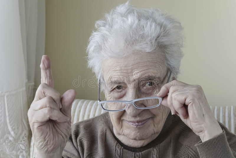 Senior woman with her finger up for admonition / warning royalty free stock photography