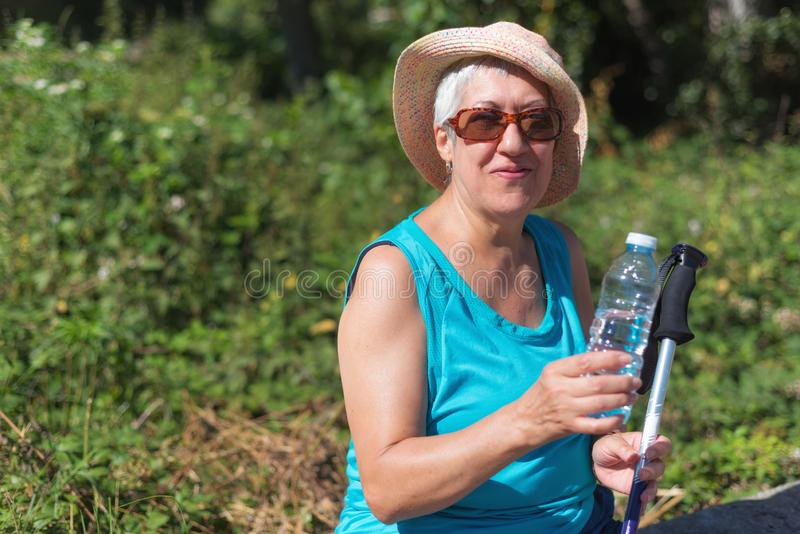 Senior woman on hike smiling and drinking water royalty free stock photos