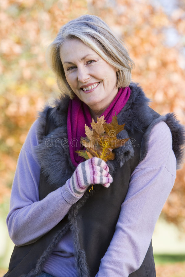 Senior woman holding autumn leaf outdoors royalty free stock image