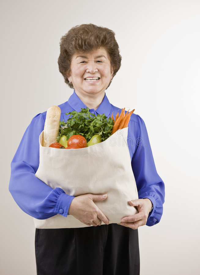 Senior woman holding bag of groceries stock image