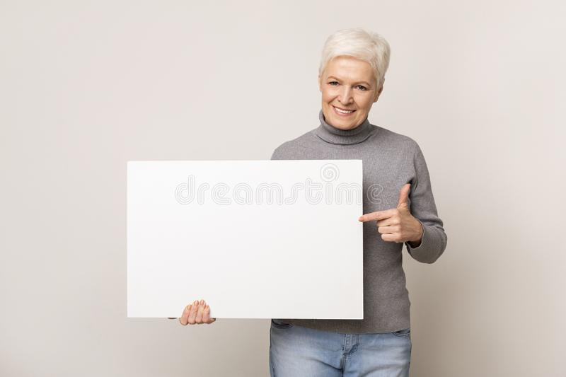Senior woman holding blank advertising board and pointing on it stock photography