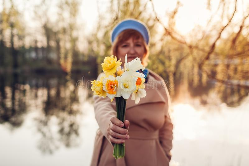 Senior woman holding bouquet of flowers. Mother`s day concept. Senior woman holding bouquet of flowers by spring river at sunset. Mother`s day concept stock photography