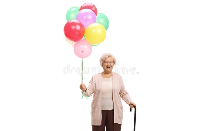Senior woman holding a bunch of balloons. Isolated on white background royalty free stock images