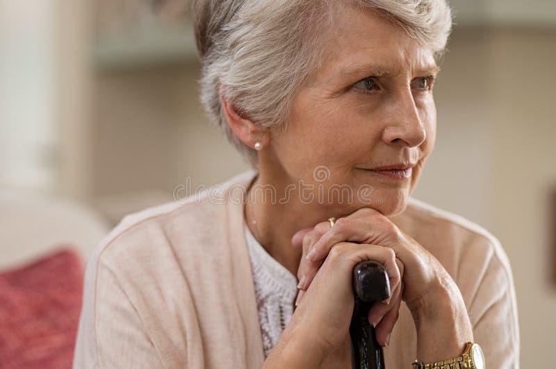 Senior woman holding cane royalty free stock photo