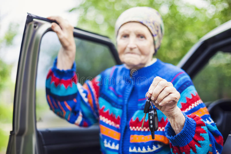 Senior woman holding car key and smiling, selective focus. Kiev, Ukraine stock photography