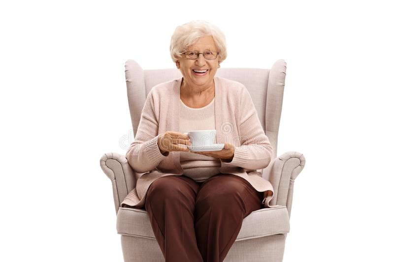 Senior woman holding a cup and sitting in an armchair. Isolated on white background stock photography