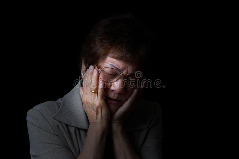 Senior woman holding face while in pain on black background stock photos