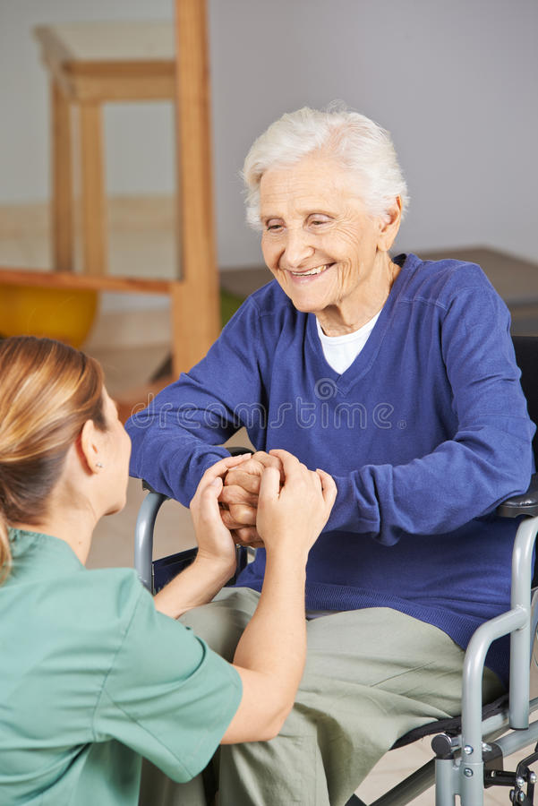 Senior woman holding hands with geriatric nurse. Happy senior women in wheelchair holding hands with geriatric nurse stock photography