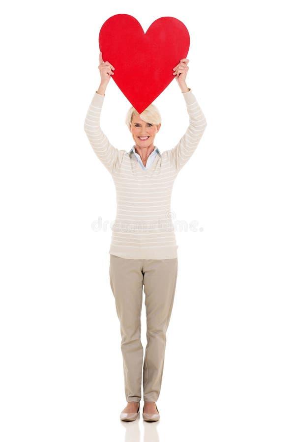 Senior woman holding heart shape royalty free stock photography