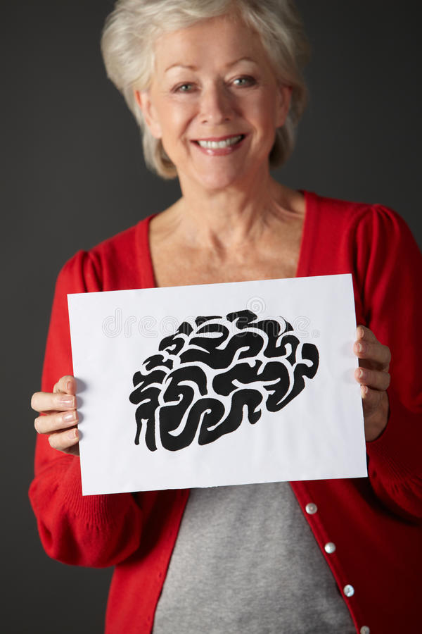 Senior woman holding ink drawing of brain stock photo