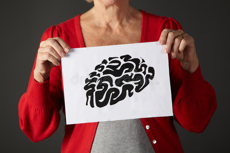 Senior woman holding ink drawing of brain. Cropped image of senior woman holding ink drawing of brain royalty free stock photo
