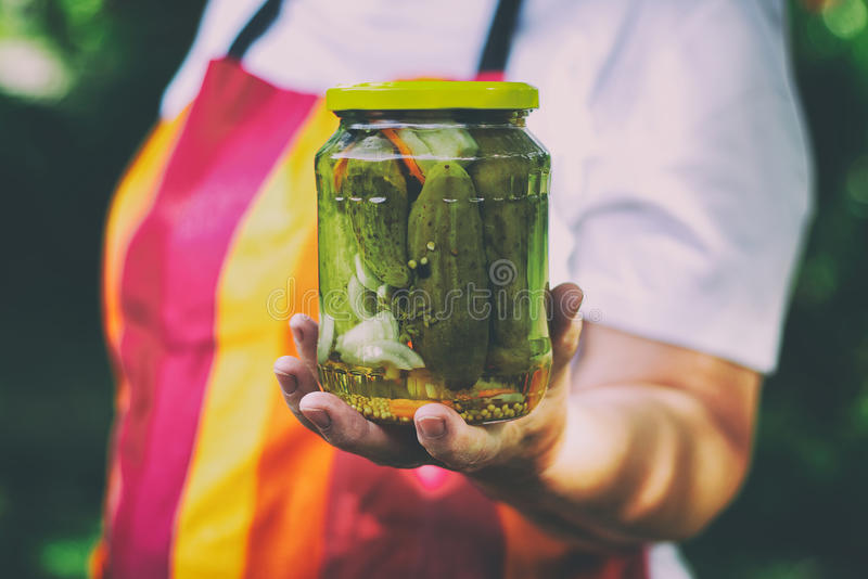 Senior woman holding a jar of pickles royalty free stock photo