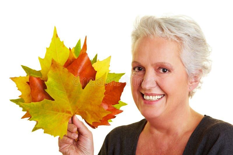 Senior woman holding maple leaves stock photography