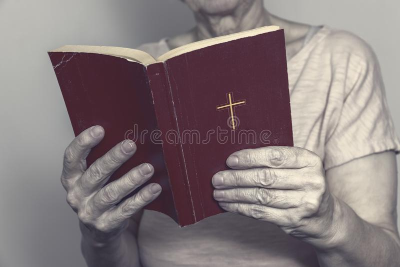 Senior woman holding an old holy bible in hands, Elder woman holding New Testament and praying stock photos