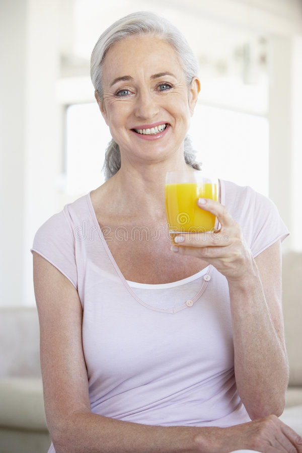 Senior Woman Holding Orange Juice And Smilng stock photography