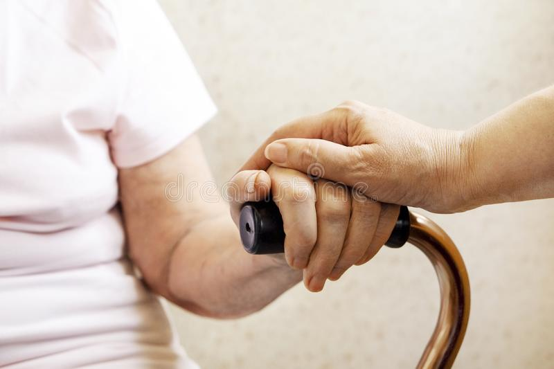 Close up of mature womans & nurse hands. Health care giving, nursing home. Parental love of grandmother. Old age related diseases. Senior woman holding quad royalty free stock photography