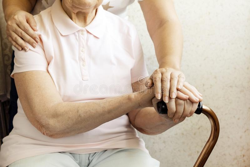Close up of mature womans & nurse hands. Health care giving, nursing home. Parental love of grandmother. Old age related diseases. Senior woman holding quad stock photography